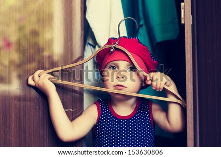 Little girl plays in wardrobe. - stock photo