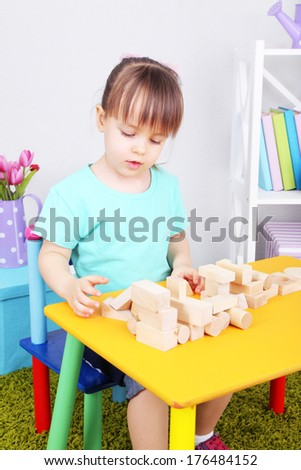 Little girl plays with construction blocks sitting at table in room