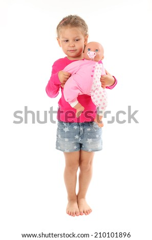 Little girl plays with favorite doll. Isolated over white background