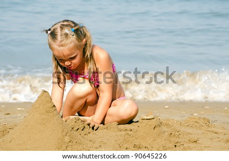 Little girl plays with sand sea coast - stock photo
