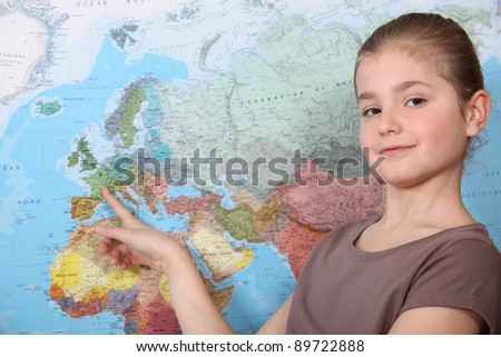 little girl pointing at a map - stock photo