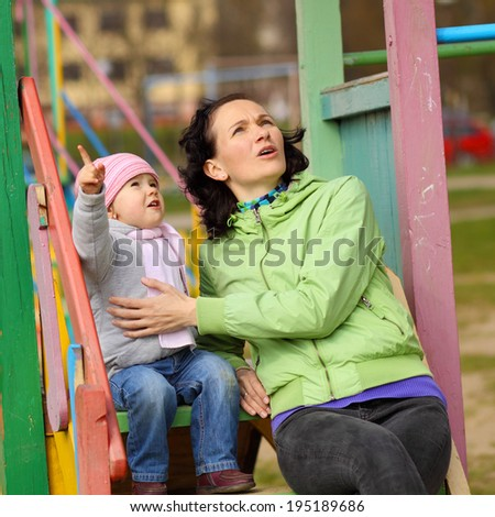 little girl pointing up emotionally for mother. Mom and girl looking up