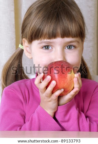 Little girl portrait eating fresh red apple. - stock photo