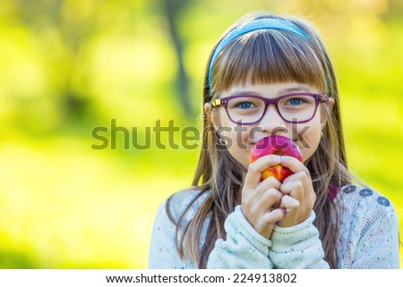 Little girl portrait eating red apple in garden. - stock photo
