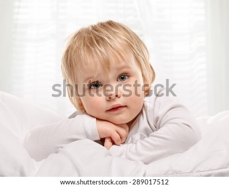 Little girl portrait on bed with light window background - stock photo