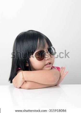 Little girl portrait wearing sun glasses - stock photo