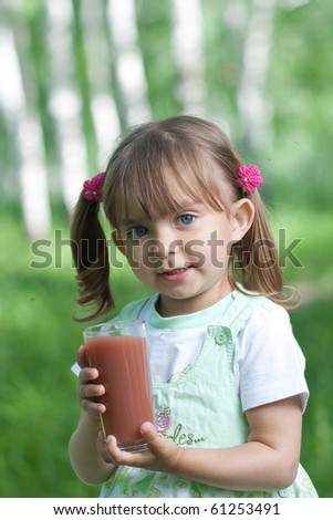 Little girl portrait with glass plum or cherry juice outdoor - stock photo