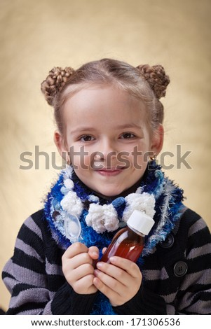 Little girl portrait with medical cough syrup in a bottle - stock photo