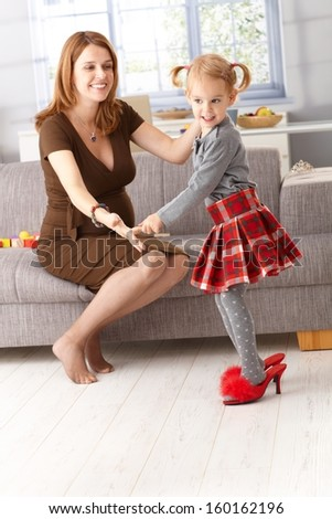 Little girl posing in mother's high heel red slippers, having fun.