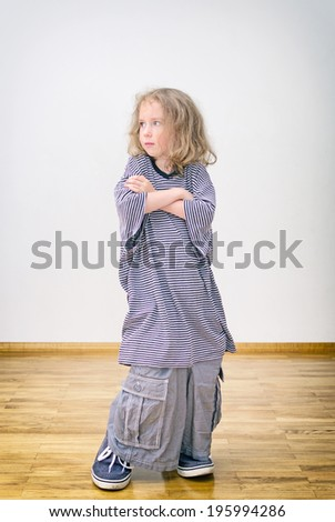 Little girl posing in oversized shorts and shirt. - stock photo