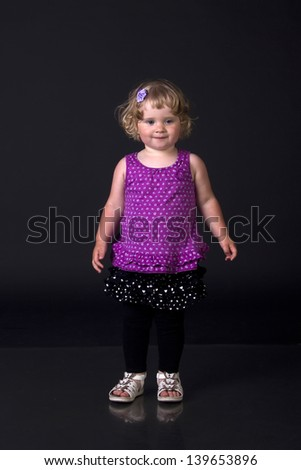 Little girl posing on a black background - stock photo
