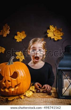 little girl posing with a wooden table with a Halloween pumpkin, leaves and lantern
