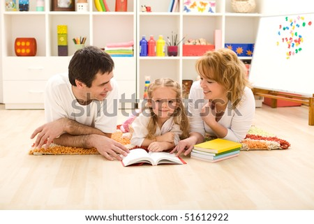 Little girl practice reading with her parents