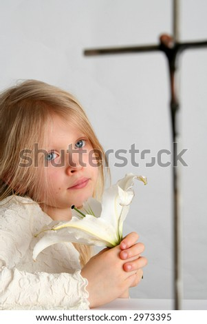 Little girl praying in front of the cross - stock photo