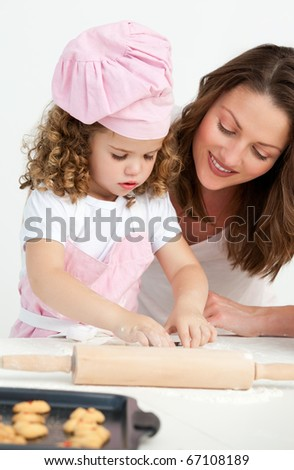 Little girl preparing a daughter with her mother in the kitchen - stock photo
