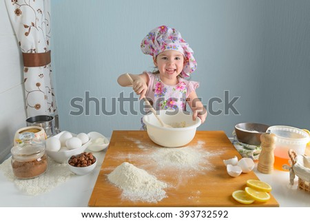 little girl preparing cakes in the kitchen - stock photo