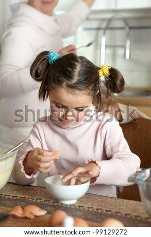 Little girl preparing eggs - stock photo