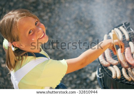 Little girl preparing meat and sausages using a barbecue grill