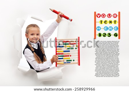 Little girl preparing to go back to school - leaning through hole in billboard - stock photo