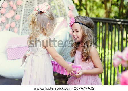 little girl present a party birthday gift to her friend - stock photo