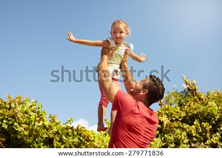Little girl pretending to be a airplane as her father lifts her in the air. Father holding his daughter up high against sky. - stock photo