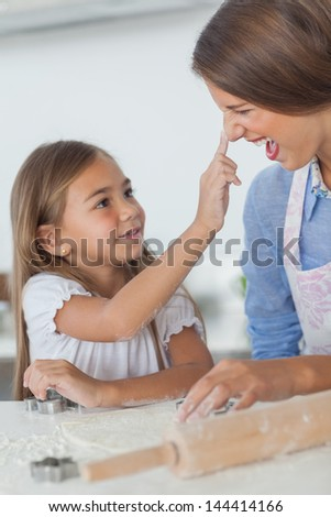 Little girl putting flour on the nose of her mother while baking - stock photo