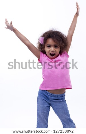 Little girl putting her hands in the air with an excited pose, almost like a dancer. - stock photo
