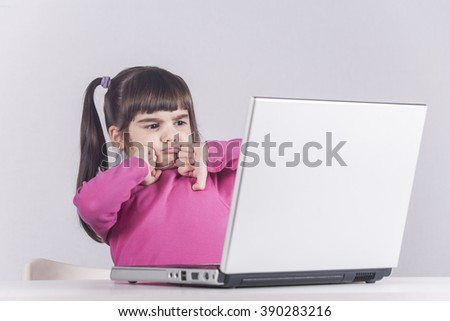 Little girl reacts while using a laptop. Internet safety concept. Toned image with selective focus