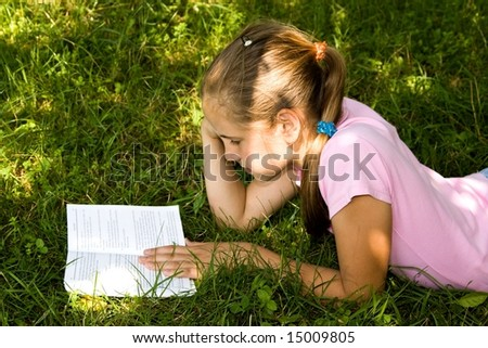 Little girl read book outdoors. - stock photo