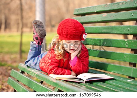 Little girl reading a book on a bench in the park in an urban neighborhood. - stock photo