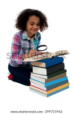 Little girl reading a book using magnifying glass - stock photo