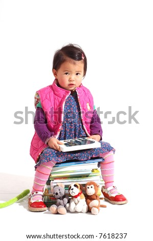 little girl reading a book while sitting on a stack of books - stock photo