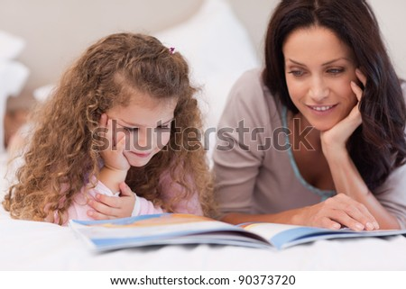 Little girl reading bedtime story with her young mother - stock photo