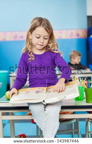 Little girl reading book while sitting on desk with friend in background at kindergarten - stock photo