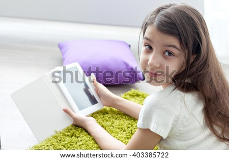 little girl reading e-book while lying on the floor.