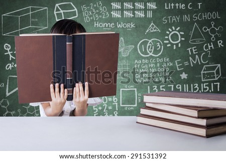 Little girl reading textbooks in the class while covering her face, shot with doodle background on the blackboard - stock photo
