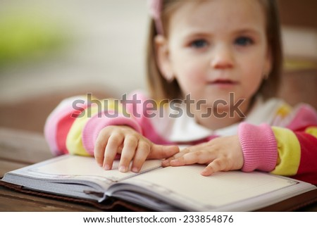 little girl reads book