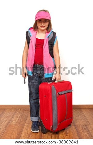 Little girl ready to travel with big red luggage - stock photo