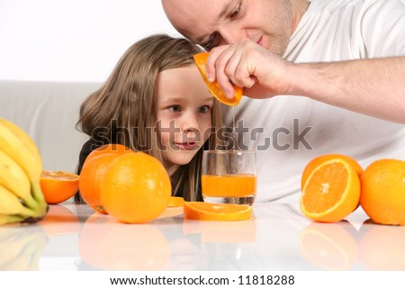 Little girl really fascinated with orange juice making. Studio shot on white background and sofa. - stock photo