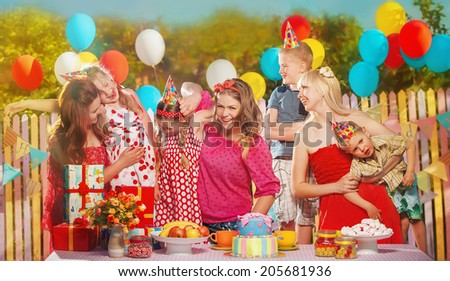 Little girl rejoice  in her birthday round about her friends - stock photo