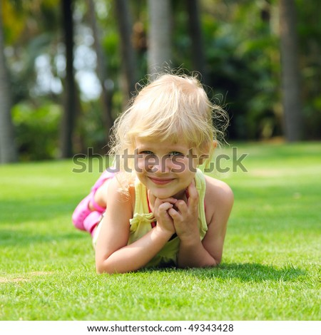 Little girl resting on meadow - stock photo