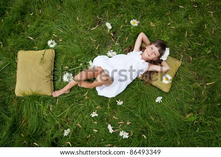 little girl resting on soft pillow in fresh spring grass - stock photo