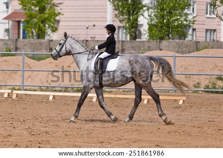 Little girl riding a horse participates in competitions. Summer, countryside, racetrack - stock photo
