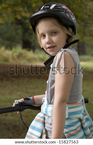 Little girl riding bike wearing helmet.