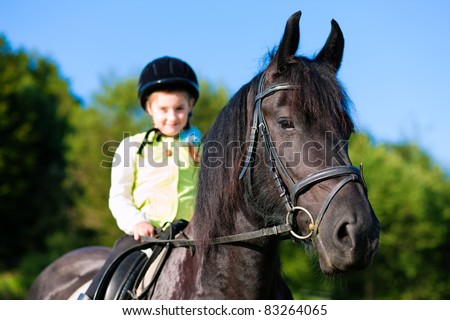 Little girl riding in summer with her horse - stock photo