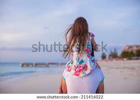 Little girl riding on her dad walking by tropical beach - stock photo