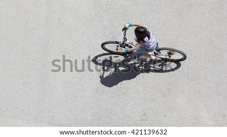 Little girl riding on the bicycle in asphalt, long shadow, top view