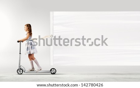 Little girl riding scooter and pulling blank banner - stock photo