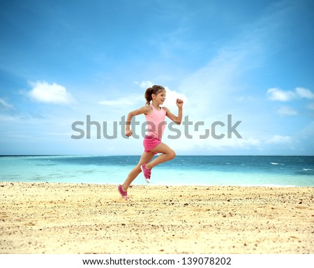 Little girl running along  ocean - stock photo