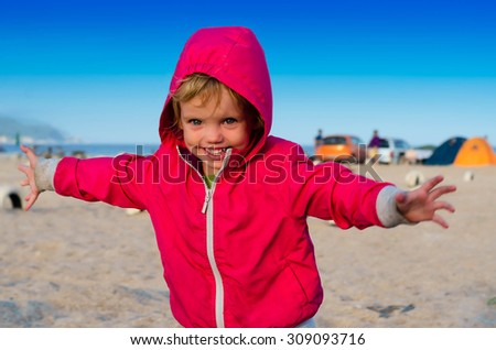 Little girl running and smiling near the camping tents on the seashore. - stock photo